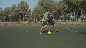 Football forward making attempt to score goal. Offensive soccer team players passing ball and moving towards goal of opposing team during football game. Young stock video footage