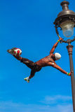 Football Freestyle Iya Traore juggling a Soccer Ball in front of. PARIS, FRANCE - MAY 4, 2014: Incredible Football Freestyle Iya Traore hanging on Lamp Post and royalty free stock photography