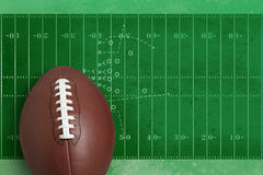 Football in front of textured field diagram. A pro style football stands in front of a a textured field with yard lines and a diagram of a play Royalty Free Stock Image