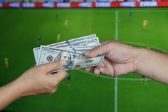 Football Gambling Concept : Hand gives money to another over TV Stock Photo