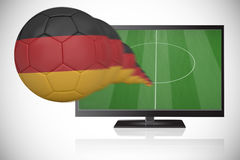 Football in germany colours flying out of tv Stock Photo