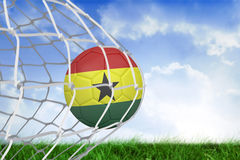 Football in ghana colours at back of net Royalty Free Stock Images