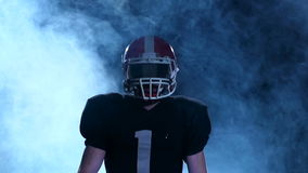 Football go out is in our protective gear in the smoke. Slow motion. Boy football player is in a protective helmet and his boxing gear through the smoke. Slow stock video footage