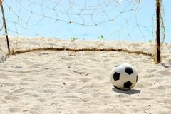 Football and goal. Football on a Beach, soccer leather ball on beach, with sea in the background royalty free stock images