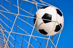 Football Goal, with blue sky. Football or soccer goal, with a neutral design ball flying into the net and blue sky in the background Royalty Free Stock Image