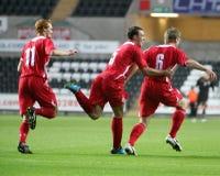 Football Goal Celebration. Christian Ribeiro (Bristol City) (right) celebrates with his team mates Shaun MacDonald (Swansea City) (left) and Darcy Blake (Cardiff Stock Images