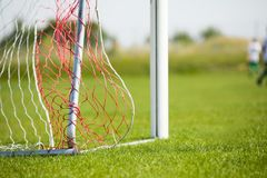 Football goal detail with a soccer players in the background. Football soccer pitch. Royalty Free Stock Images