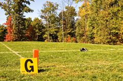 Football Goal Line and Helmet. A football helmet lies on the ground in the end zone during half-time of a youth league football game on a fall morning Royalty Free Stock Image