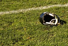 Football Goal Line and Helmet. A football helmet lies on the ground in the end zone during half-time of a youth league football game Stock Image