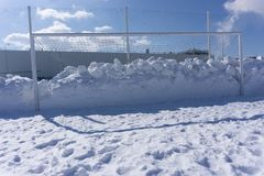 Football goal littered with snow winter field . stock images