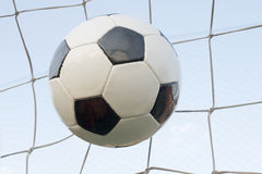 Football in the goal net. Soccer ball in the goal net against the sky Stock Images
