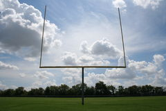 Football Goalposts. View of American football goalposts from the endzone, with a brilliant sky full of fluffy clouds in the background Royalty Free Stock Photos