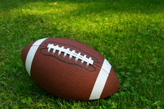 Football on grass. American football isolated on top of green grass stock photography