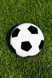 Football on grass. Overhead view of black and white football or soccer ball on grass Stock Image