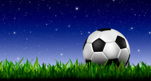 Football in green grass. Over a twilight sky Stock Images