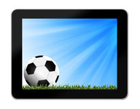 Football in green grass with background in tablet-pc Stock Image