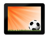 Football in green grass with background in tablet-pc Royalty Free Stock Photo