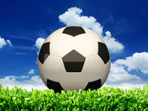 Football on green grass and blue sky Royalty Free Stock Image