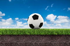 Football on green grass with soil on blue sky Royalty Free Stock Images