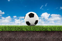Football on green grass with soil on blue sky Royalty Free Stock Photography