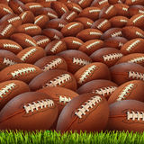 Football Group. On a grass field as an infinite background for sports and fitness symbol of an American team leisure activity playing with leather oval pigskin Stock Photos