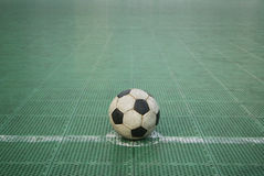 Football. Grunge football on green plastic court Royalty Free Stock Image