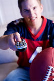 Football: Guy Holds Remote Control And Watches Team On TV Stock Photo