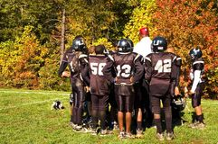 Football Half-time Pep Talk - 3. Coach gives last minute instructions at half-time during a youth league football game on a Saturday morning in the fall.  They Stock Photography