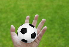 Football in hand with grass Royalty Free Stock Photography