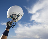 Football Helmet. A football player raises his helmet in triumph with a simple blue sky background. Photo includes Clipping path Stock Images
