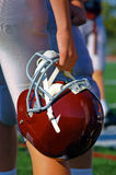 Football helmet. A football player holds his helmet while watching from the sideline Royalty Free Stock Photos