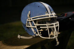 Football helmet. Blue American football helmet sitting on a wooden bench Royalty Free Stock Photos