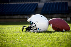 Football Helmet Background. A football and a helmet rest on a football field prior to game day Stock Photo