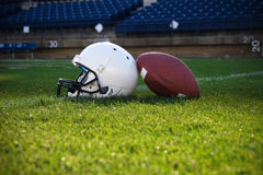 Football Helmet and ball. A football helmet  and ball rest on the field in a stadium. Copy space below Stock Photos