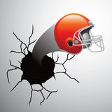 Football helmet coming out of cracked wall Royalty Free Stock Photography