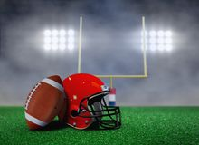 Football and Helmet on Field with Goal Post. Under Spotlights Royalty Free Stock Photos