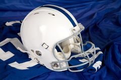 Football Helmet and Jersey. White football helmet with blue stripe sitting on a blue jersey with number 27 Royalty Free Stock Images