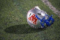 Football Helmet. A lone football helmet lying on the field royalty free stock images