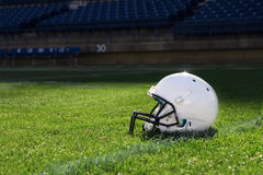 Football Helmet at the Stadium. A football helmet rest on the field in a stadium. Copy space to the left Stock Image
