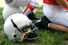 Football and Helmets. Football players sitting on helmets royalty free stock photos