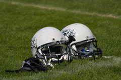 Football helmets. Two football helmets placed side by side on the playing field Stock Photography