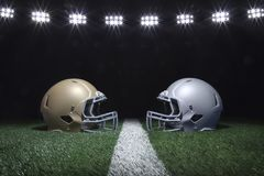 Football helmets facing off on a yard line below stadium lights Royalty Free Stock Image