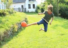 Football - high kick. Barefoot boy - kid playing football and kicking orange ball in high jump Royalty Free Stock Image