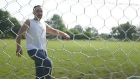 Football hitting the back of the net in slow motion stock footage