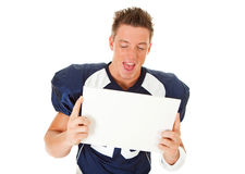 Football: Holding Blank Sign. Caucasian American football player, in uniform, isolated on white, with various related props Royalty Free Stock Photography