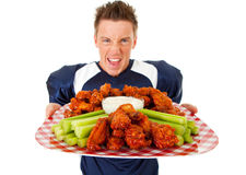 Football: Holding Platter of Chicken Wings. Caucasian American football player, in uniform, isolated on white, with various related props Royalty Free Stock Image