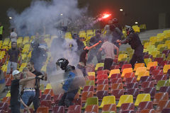 Football hooligans fight against constabulary forces. Gendarmerie officers trying to restore public order during the football match between Dinamo Bucharest and Royalty Free Stock Images