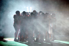 Football Huddle in fog. American football players in a huddle before the game in an arena filled with fog royalty free stock photography