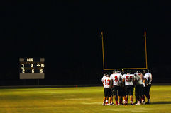 Football huddle at night game