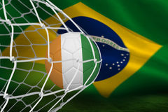 Football in ivory coast colours at back of net Stock Images
